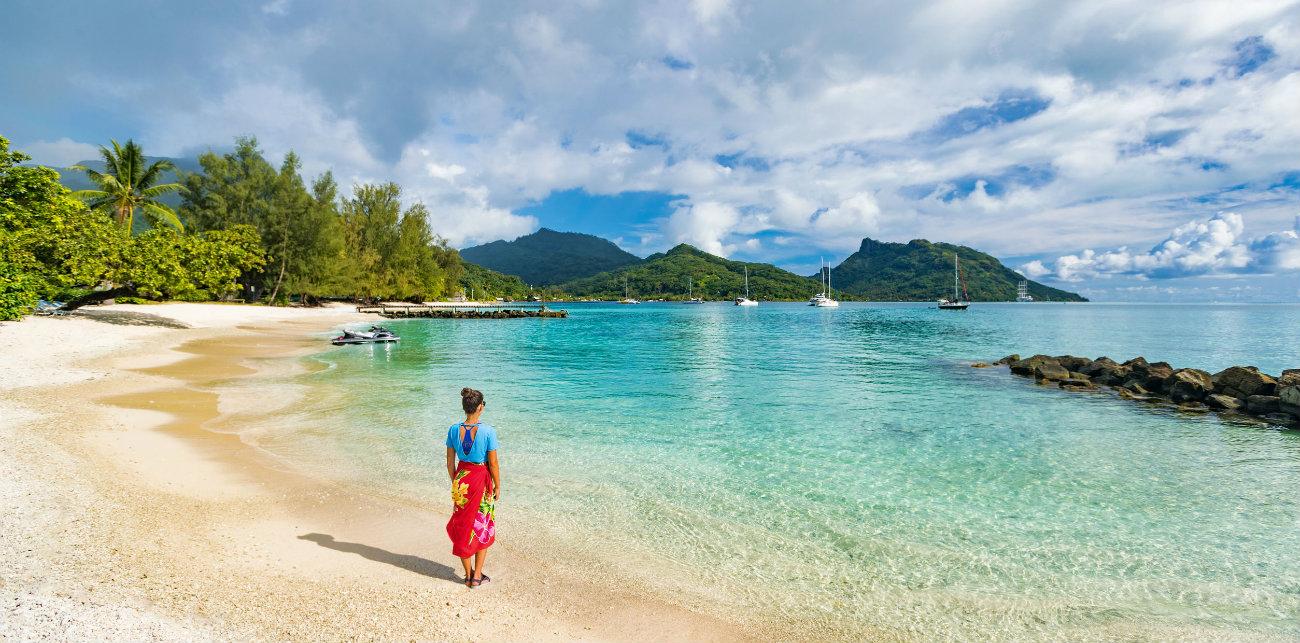 Mujer paseando en la Playa de la Polinesia Francesa página de incio