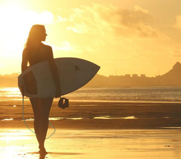 Mujer con tabla de surf en el borde de la playa