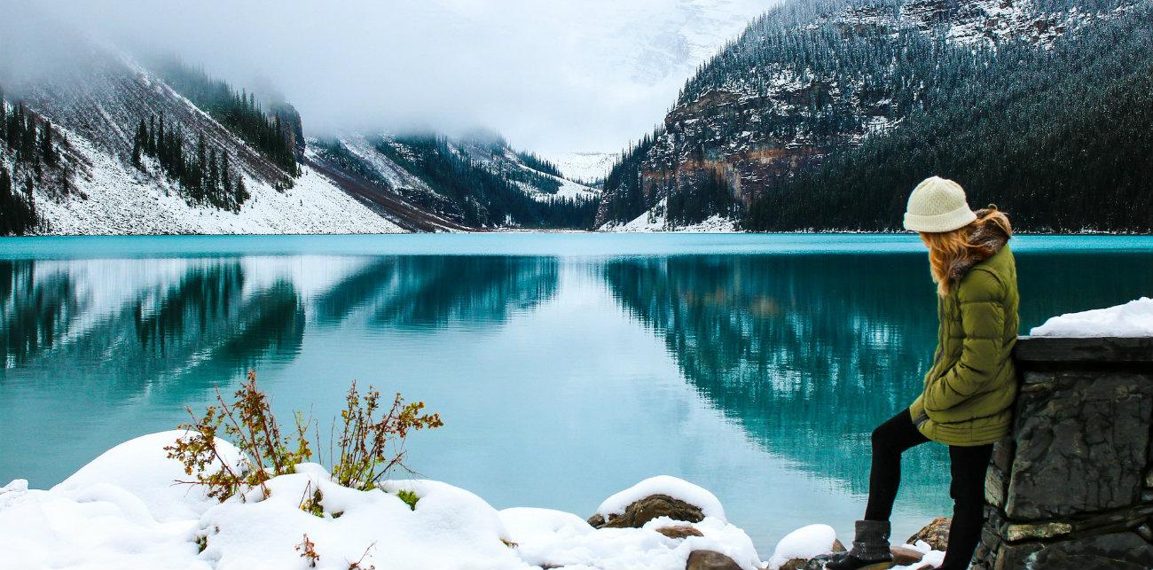 Mujer en la montaña con nieve y lago página inicial